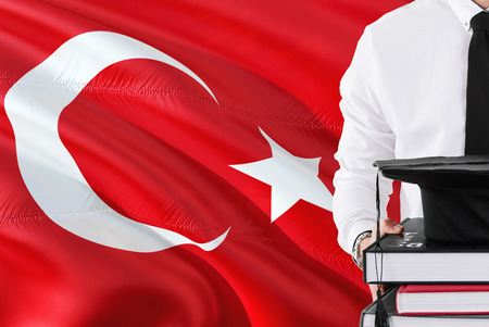 Successful Turkish student education concept. Holding books and graduation cap over Turkey flag background.
