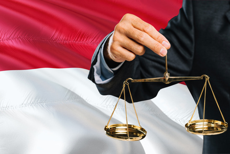 Indonesian Judge is holding golden scales of justice with Indonesia waving flag background. Equality theme and legal concept. 免版税图像