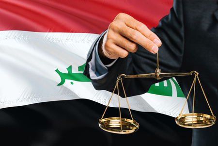 Iraqi Judge is holding golden scales of justice with Iraq waving flag background. Equality theme and legal concept.