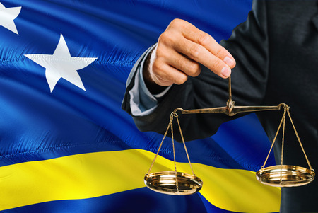 Judge is holding golden scales of justice with Curacao waving flag background. Equality theme and legal concept.