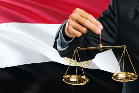 Egyptian Judge is holding golden scales of justice with Egypt waving flag background. Equality theme and legal concept.
