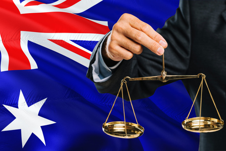 Australian Judge is holding golden scales of justice with Australia waving flag background. Equality theme and legal concept.