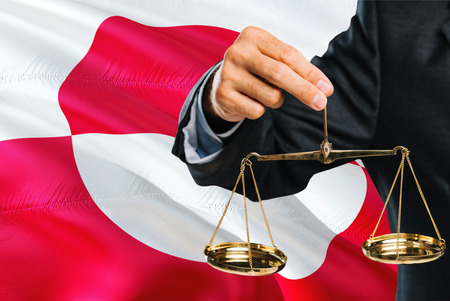 Judge is holding golden scales of justice with Greenland waving flag background. Equality theme and legal concept.