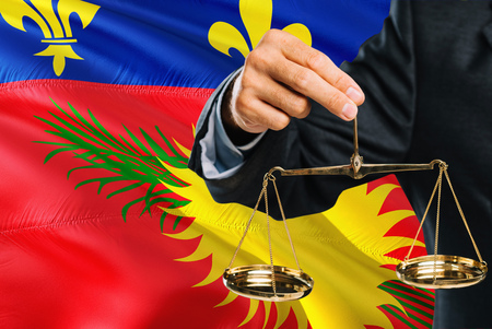 Judge is holding golden scales of justice with Guadeloupe waving flag background. Equality theme and legal concept.