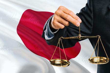 Le juge japonais tient une balance dorée de la justice avec un fond de drapeau ondulant du Japon. Thème de l'égalité et concept juridique.