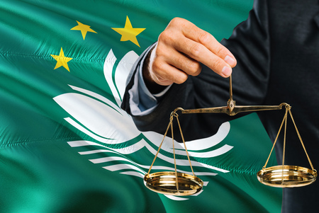 Macau Judge is holding golden scales of justice with Macao waving flag background. Equality theme and legal concept. Banque d'images - 122649427