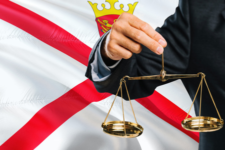 Judge is holding golden scales of justice with Jersey waving flag background. Equality theme and legal concept.