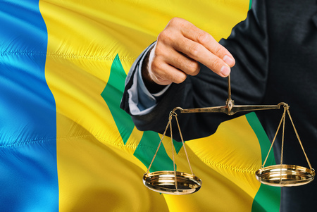 Judge is holding golden scales of justice with Saint Vincent And The Grenadines waving flag background. Equality theme and legal concept.