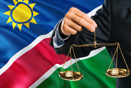 Namibian Judge is holding golden scales of justice with Namibia waving flag background. Equality theme and legal concept.