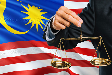 Malaysian Judge is holding golden scales of justice with Malaysia waving flag background. Equality theme and legal concept. 免版税图像