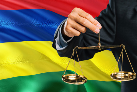 Mauritian Judge is holding golden scales of justice with Mauritius waving flag background. Equality theme and legal concept.