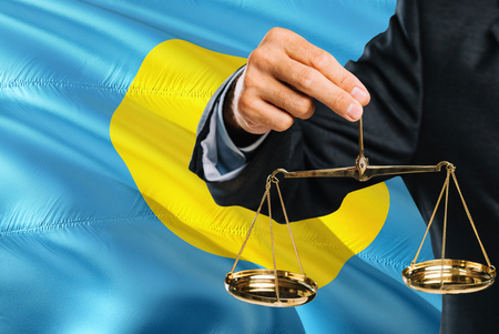 Palauan Judge is holding golden scales of justice with Palau waving flag background. Equality theme and legal concept. 免版税图像
