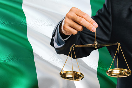 Nigerian Judge is holding golden scales of justice with Nigeria waving flag background. Equality theme and legal concept.