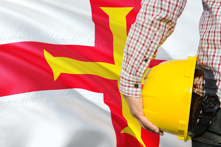 Engineer is holding yellow safety helmet with waving Guernsey flag background. Construction and building concept.