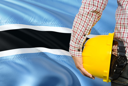 Engineer is holding yellow safety helmet with waving Botswana flag background. Construction and building concept.