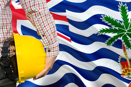 Engineer is holding yellow safety helmet with waving British Indian Ocean Territory flag background. Construction and building concept. Stock Photo