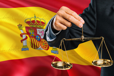 Spanish Judge is holding golden scales of justice with Spain waving flag background. Equality theme and legal concept.