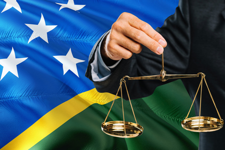 Judge is holding golden scales of justice with Solomon Islands waving flag background. Equality theme and legal concept. Imagens