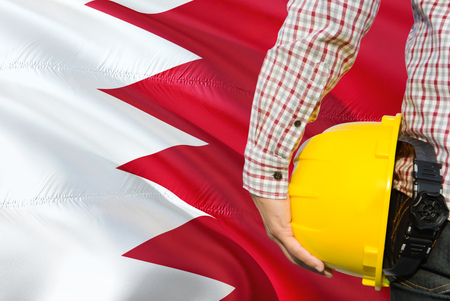Bahraini Engineer is holding yellow safety helmet with waving Bahrain flag background. Construction and building concept. Stock Photo