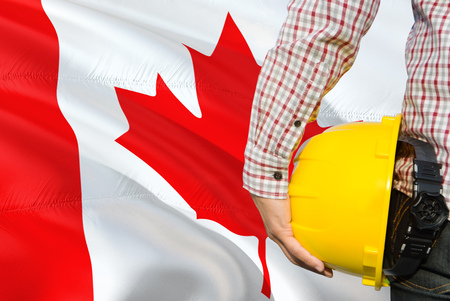 Canadian Engineer is holding yellow safety helmet with waving Canada flag background. Construction and building concept. Stockfoto