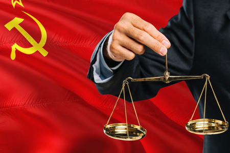Judge is holding golden scales of justice with Soviet Union waving flag background. Equality theme and legal concept.