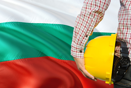 Bulgarian Engineer is holding yellow safety helmet with waving Bulgaria flag background. Construction and building concept.