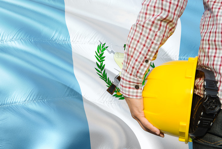Guatemalan Engineer is holding yellow safety helmet with waving Guatemala flag background. Construction and building concept. Stock Photo