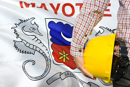 Engineer is holding yellow safety helmet with waving Mayotte flag background. Construction and building concept.