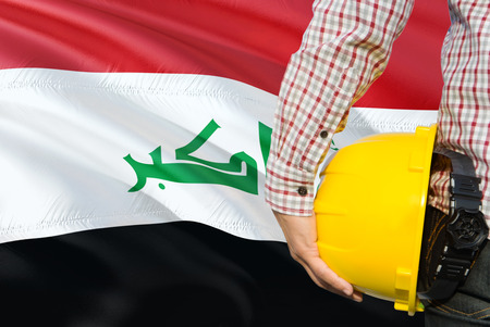 Iraqi Engineer is holding yellow safety helmet with waving Iraq flag background. Construction and building concept.