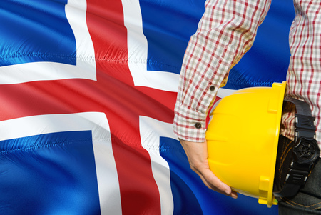Engineer is holding yellow safety helmet with waving Iceland flag background. Construction and building concept.