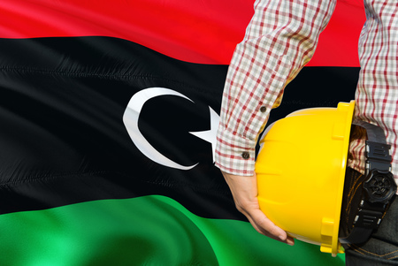 Libyan Engineer is holding yellow safety helmet with waving Libya flag background. Construction and building concept.
