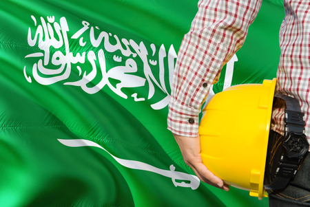 Saudi Engineer is holding yellow safety helmet with waving Saudi Arabia flag background. Construction and building concept.