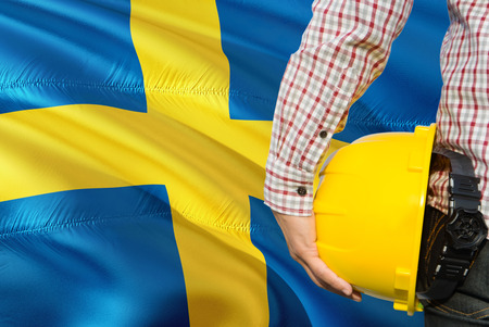 Swedish Engineer is holding yellow safety helmet with waving Sweden flag background. Construction and building concept.