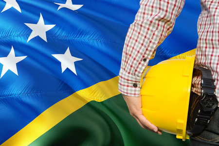 Engineer is holding yellow safety helmet with waving Solomon Islands flag background. Construction and building concept.