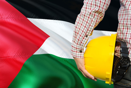 Palestinian Engineer is holding yellow safety helmet with waving Palestine flag background. Construction and building concept.