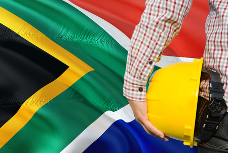 Engineer is holding yellow safety helmet with waving South Africa flag background. Construction and building concept. 免版税图像