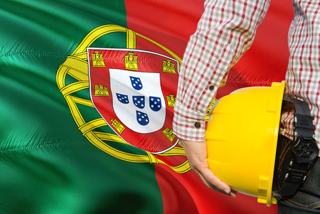 Portuguese Engineer is holding yellow safety helmet with waving Portugal flag background. Construction and building concept.