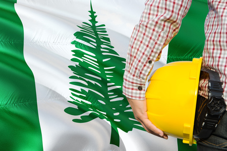 Engineer is holding yellow safety helmet with waving Norfolk Island flag background. Construction and building concept.