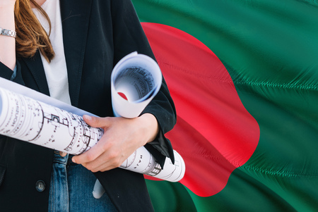 Architect woman holding blueprint against Bangladesh waving flag background. Construction and architecture concept. Stock Photo
