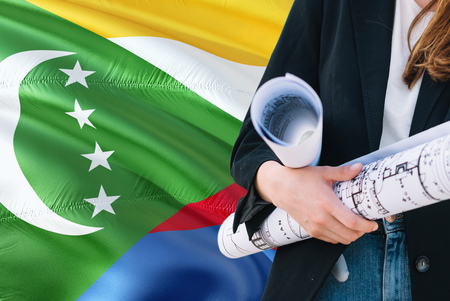 Comoran Architect woman holding blueprint against Comoros waving flag background. Construction and architecture concept.