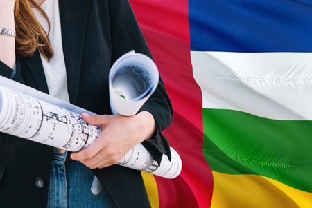 Architect woman holding blueprint against Central African Republic waving flag background. Construction and architecture concept.