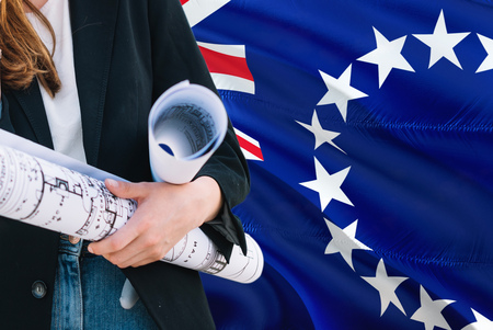 Architect woman holding blueprint against Cook Islands waving flag background. Construction and architecture concept. Imagens