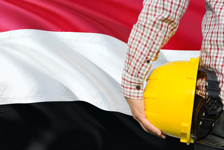 Yemeni Engineer is holding yellow safety helmet with waving Yemen flag background. Construction and building concept.