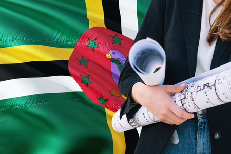 Dominican Architect woman holding blueprint against Dominica waving flag background. Construction and architecture concept.
