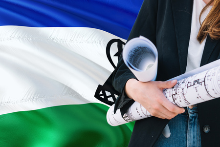 Architect woman holding blueprint against Lesotho waving flag background. Construction and architecture concept.