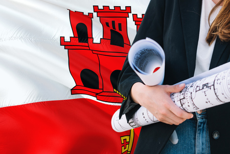 Architect woman holding blueprint against Gibraltar waving flag background. Construction and architecture concept.