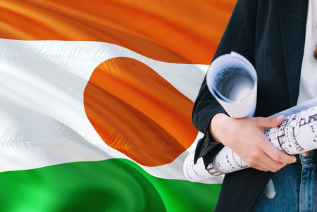 Nigerien Architect woman holding blueprint against Niger waving flag background. Construction and architecture concept.