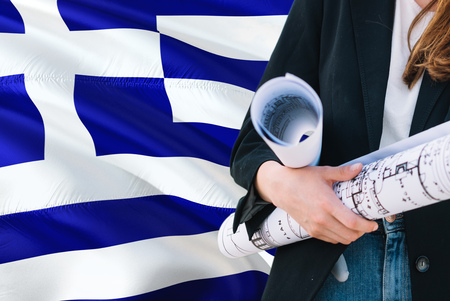 Greek Architect woman holding blueprint against Greece waving flag background. Construction and architecture concept. Stockfoto