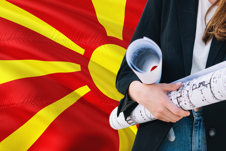 Macedonian Architect woman holding blueprint against Macedonia waving flag background. Construction and architecture concept.