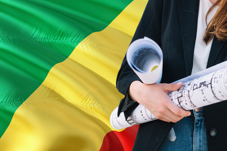 Architect woman holding blueprint against Republic Of The Congo waving flag background. Construction and architecture concept. 版權商用圖片
